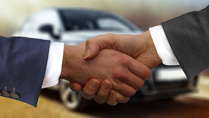 Handshake with car in the background
