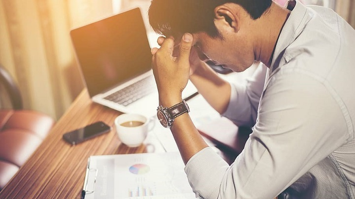 Stressed worker with head in hands