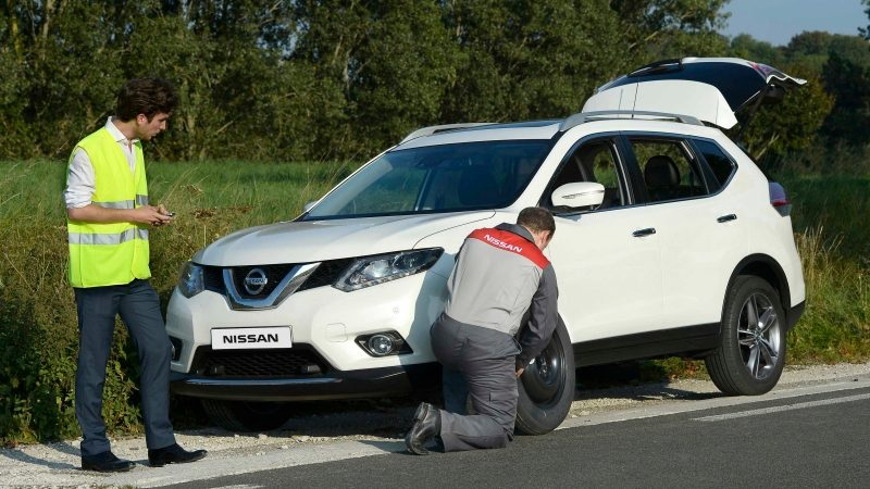 Nissan Roadside Assistant helping repair a vehicle on side of the road