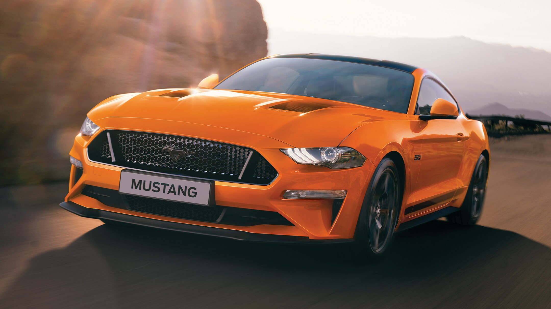 New Orange Ford Mustang being driven on country roads