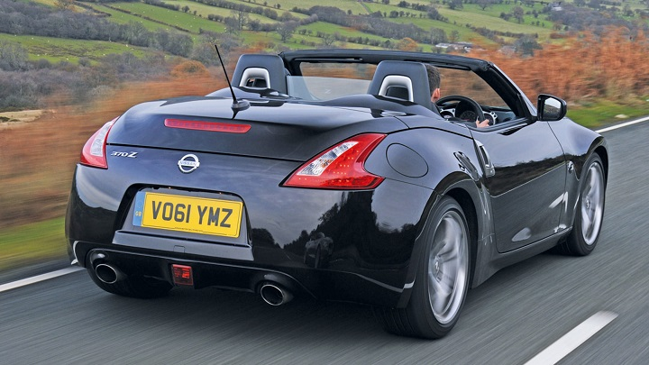 Black Nissan 370z Roadster with soft top roof down rear shot
