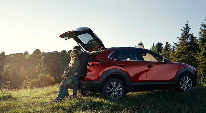 Man and woman sitting against CX-30's open boot lid in countryside