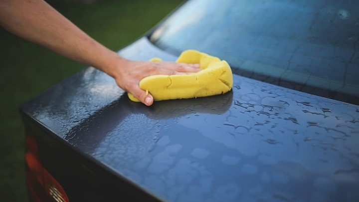 Cleaning car with yellow sponge
