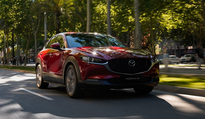 New Generation Mazda CX-30 compact crossover driving on road.