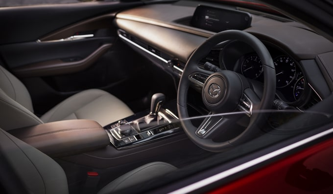 All-New Mazda CX-30 interior shot with front seats, steering wheel, dashboard and gearshift in view.