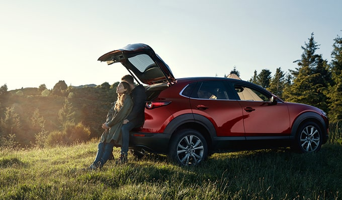 Man and woman sitting against open Mazda CX-30 boot in countryside.