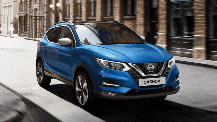 New Nissan Qashqai in Vivid Blue driving down high street using new 1.3-litre engine